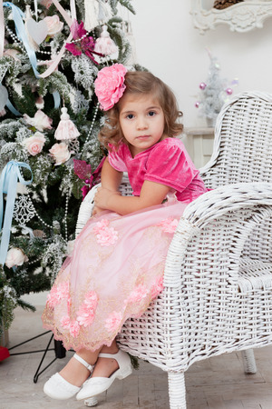 sits on a chair: Girl in an elegant dress sits in a chair near a Christmas fir-tree