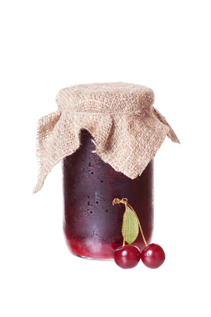 Red ripe cherries and a glass jar with cherry jam photo