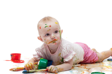Little girl soiled by multi-colored paints on a white background