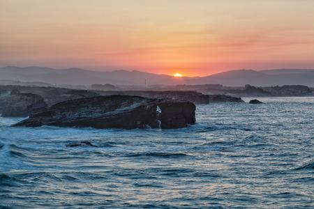 arcos de piedra: Hermosos arcos puesta de sol y piedra en Playa de las Catedrales durante entrada, Espa�a