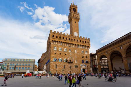 ITALY, FLORENCE - MAY 8, 2014: Tourists on Signoria Square near Palazzo Vecchio.Palazzo Vecchio (Italian pronunciation:Old Palace) is the town hall of Florence, Italy Editorial