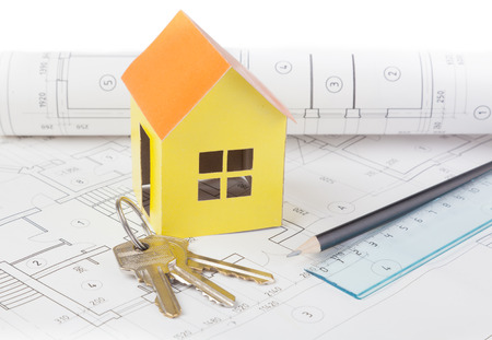 Paper model of the house costs on the construction plan, keys lie nearby photo
