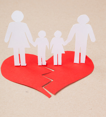 Divorce effect on kids concept with hands cutting paper people family Stock Photo