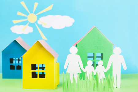 home insurance: paper family is holding hands beside their new paper house Stock Photo
