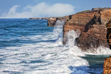 oceanic: Oceanic waves break about coastal rocks
