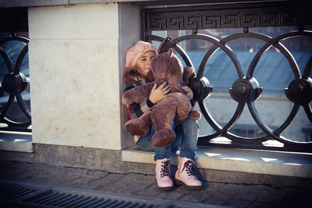 art processing: little girl in a pink beret sits at a fencing of the bridge and holds a toy bear in hand. Art processing: toning, vignetting