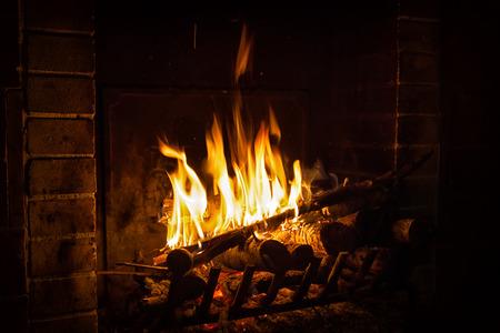 helle Feuerflamme brennt in einem Kamin im alten Haus im Winter am Abend