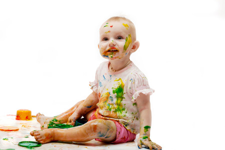 Baby soiled by paint lodges on a light background photo