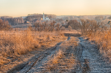 pacification: Rural landscape with the road, a grass covered with hoarfrost and church in the distance at sunrise in the spring