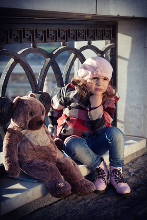 parapet: sad girl in a pink beret sits on a parapet with big toy a bear. Stock Photo