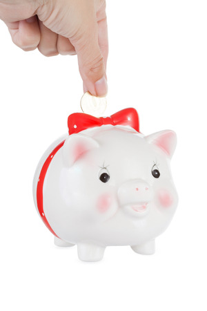 abbassa: hand lowers a coin in a pig moneybox, is isolated on a white background