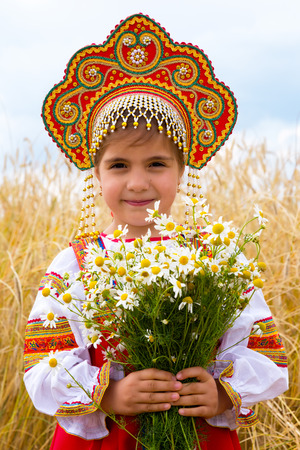 kokoshnik: Girl in the Russian national sundress and a kokoshnik to stand in the field with a bouquet of camomiles Stock Photo