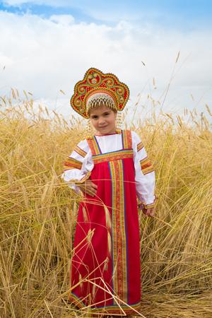 kokoshnik: little girl in Russian national a sundress and a kokoshnik stand in a wheat field in summer day Stock Photo