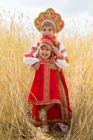 utmost: Two girls in the Russian national sundresses play a field of ripe wheat