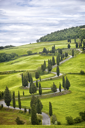 Beautiful landscape of Tuscany with the twisting road and cypresses Stock Photo