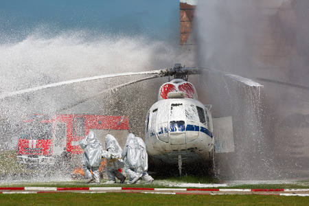 accident fire truck: Firefighters in special suits extinguish the fire by helicopter