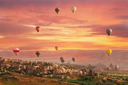 fly: Multi-colored air shata fly over rocks in Cappadocia at sunrise Stock Photo