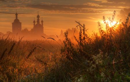 Silhouet van de kerk in ochtendmist bij zonsopgang