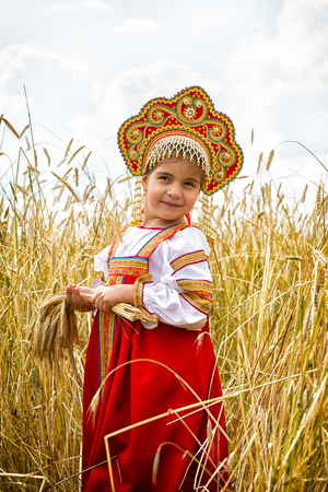 utmost: girl in Russian national a dress with ears in hands stand in the field of the ripening wheat