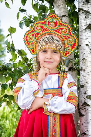 kokoshnik: little girl in Russian national a sundress and a kokoshnik stand near a birch in summer day Stock Photo
