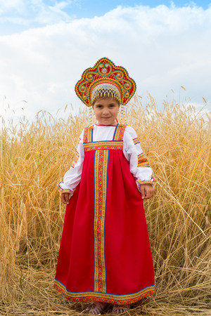 kokoshnik: girl in Russian national a dress with ears in hands stand in the field of the ripening wheat