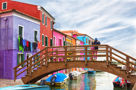 old photograph: Girl tourist standing on a wooden bridge and photographs colored houses on the island of Burano, Venice, Italy Stock Photo