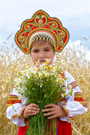Girl in the Russian national sundress and a kokoshnik to stand in the field with a bouquet of camomiles photo