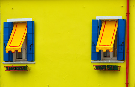 awnings: Two windows with blue shutters and awnings on the yellow wall, Burano, Venice
