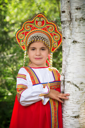 kokoshnik: little girl in Russian national a sundress and a kokoshnik stand near a birch in summer day; Stock Photo