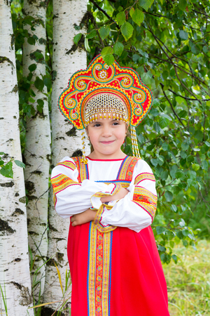 little girl in Russian national a sundress and a kokoshnik stand near a birch in summer day; photo