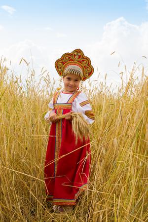 kokoshnik: Girl in Russian national sarafan and a kokoshnik standing in a wheat field in summer day Stock Photo