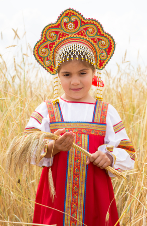 utmost: Girl in Russian national sundress standing in a wheat field and holding ears of corn Stock Photo