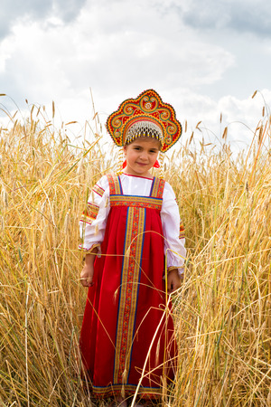 Girl in Russian national sundress standing in a wheat field photo