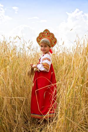 kokoshnik: Girl in Russian national sarafan and a kokoshnik standing in a wheat field