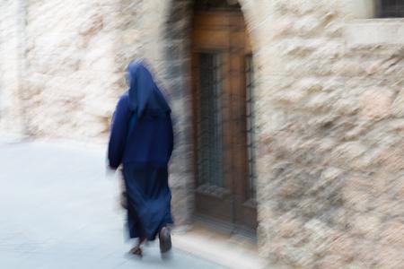 religious habit: Nun walking down the street. blur effect