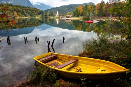 Yellow boat on Lake Bohinj, in the background the church and stone bridge