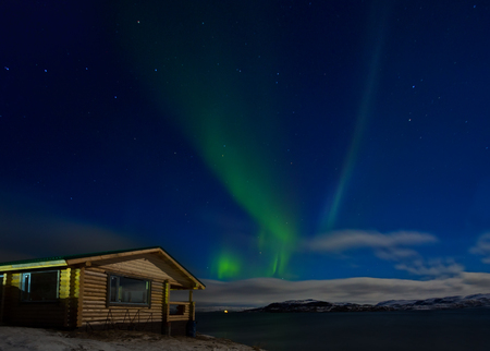 Landscape with a wooden house and aurora