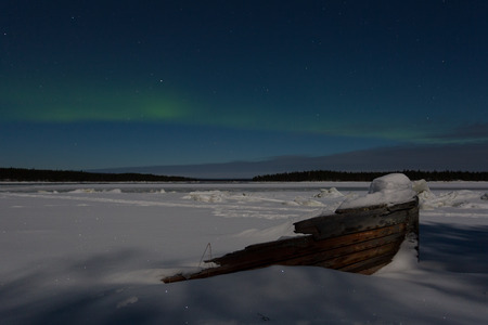 ionosphere: Old wooden boat in the snow on a background of aurora