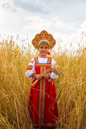 Littl girl in Russian national sarafan and a kokoshnik standing in a wheat field in summer day