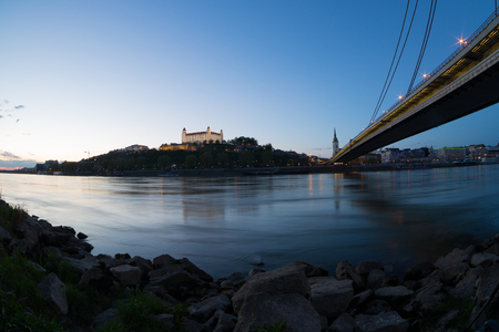 View of a medieval castle in Bratislava from under the bridge through river  Danube Stock Photo