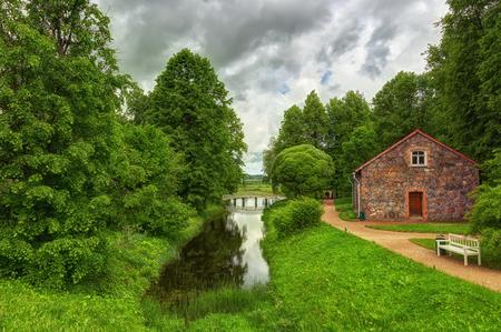 Landscape with small wooden bridge and a stone barn in Mikhaylovskoye  in Pskov Region, Russia