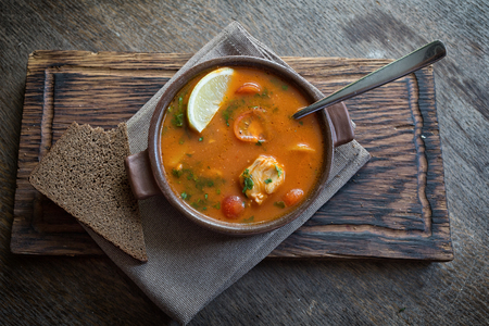 Marmitako soup in a ceramic bowl on a wooden board, next to a piece of bread Stock Photo