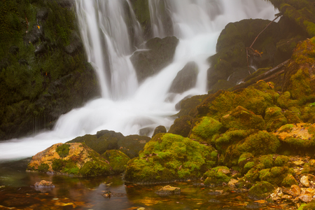 waterfall among rocks covered with green moss