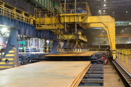 Overhead crane with magnetic lift in the shop for manufacturing large diameter pipes