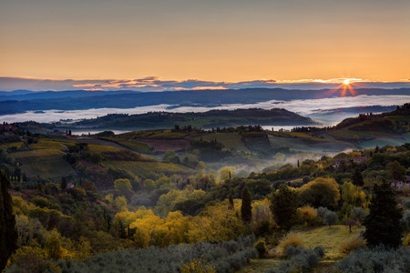 Landscape with a morning fog and sunrise in the vicinity of the city of San Gimignano, Tuscany
