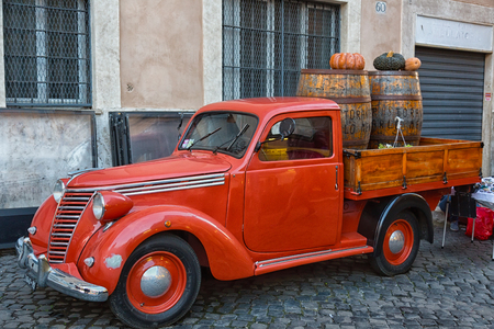 ITALY, ROME - OCTOBER 02, 2015: The old orange Fiat car is used as advertising in the vegetable market