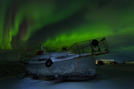 Old fishing boat on a background of aurora in winter Stock Photo