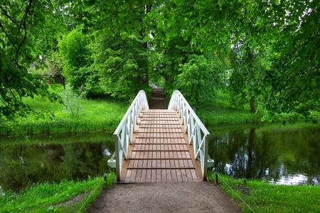 White wooden bridge in the old park in the village of Mikhailovskoye, Pskov region, Russia