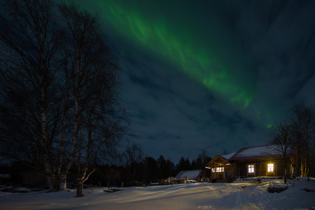 Old wooden houses in the village and the aurora borealis in the sky, Russia Stock Photo