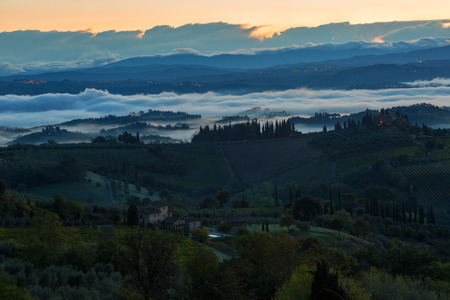 Landscape with a morning fog and vineyards in the vicinity of the city of San Gimignano, Tuscany Stock Photo